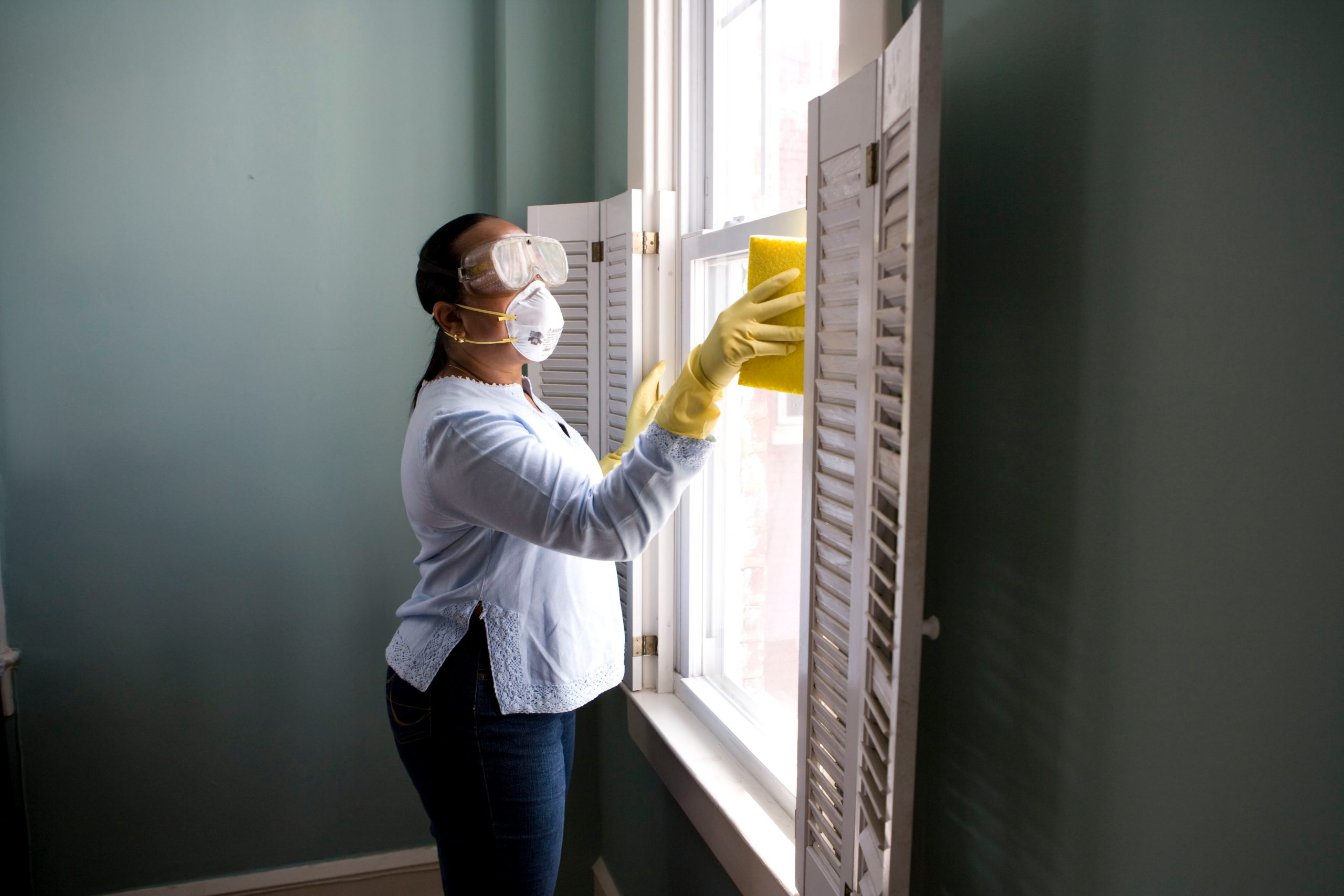 woman cleaning windows with gloves and mask